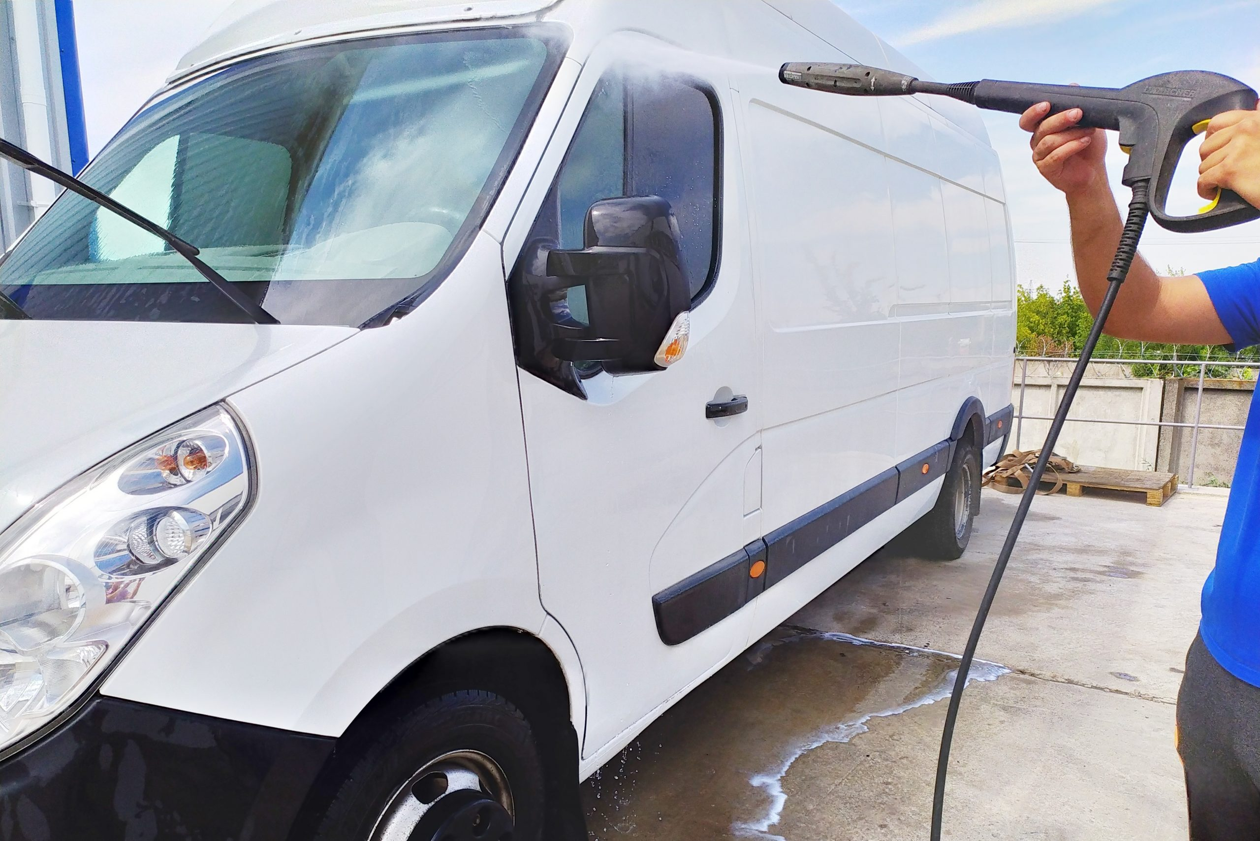 High pressure water jet cleaning. A male car wash's worker washing a white minibus using power sprayer.