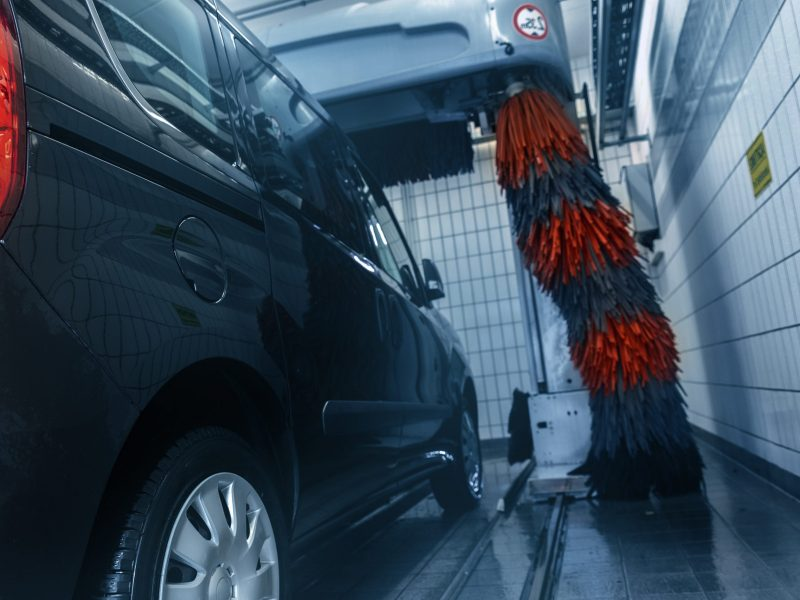 Black modern delivery minivan car cleaning with robot automatic tunnel car wash machine. Grey and red soft brushes washing vehicle with foam at gas petrol service cleaner station. Carwash business.